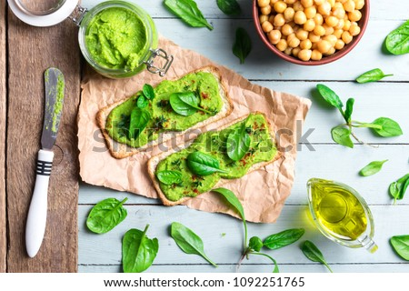Two crackers with green spinach humus on wooden table. Flat lay. Hummus concept. Food photography