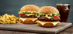 Two craft beef burgers on wooden table on blue background.