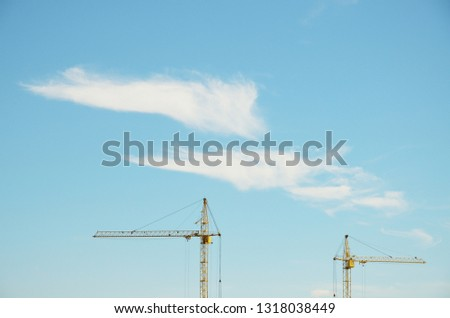 Two cranes at background of blue sky with clouds. Upper part of two tower cranes at background of sky. Two white cirrus clouds in light blue sky. Side view.