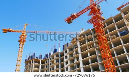 Two cranes near building. Concrete building under construction. #729096175