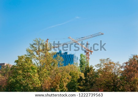 Two cranes working on the construction site near modern building and city park. Sunny day with blue sky. #1222739563