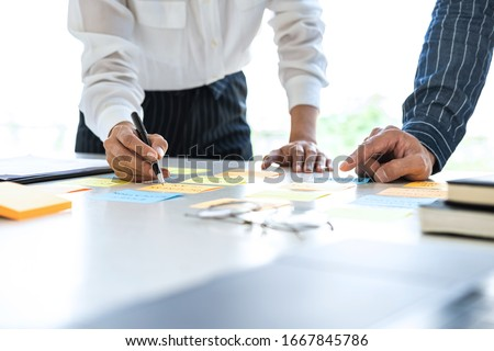 Two creative business people meeting and planning use post it notes sticky note on desk to share idea, Analysis data chart and graph with teamwork strategy brainstorming in office.