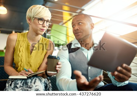 Two creative millenial small business owners working on social media strategy using a digital tablet while sitting in staircase #437276620