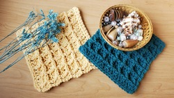 Two crocheted, cotton hot pads, one in blue and one yellow, against a wooden backdrop, with a mini wooden basket of sea shells and pearls on the blue, and a bunch of blue floral sprigs on the yellow.