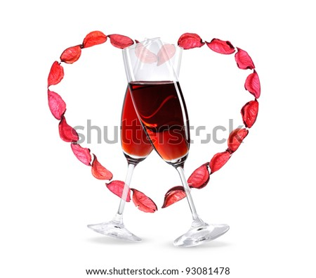 Two crossed wineglasses with red wine and a heart shape made from rose petals. Isolated on white background. Love, Valentine's Day concept.