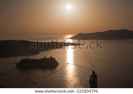 Two cruise ships anchored in the caldera of Santorini in the Greek islands as dusk descends