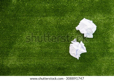 Two crumpled paper ball on green grass