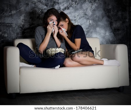 Two crying girls looks TV in dark room