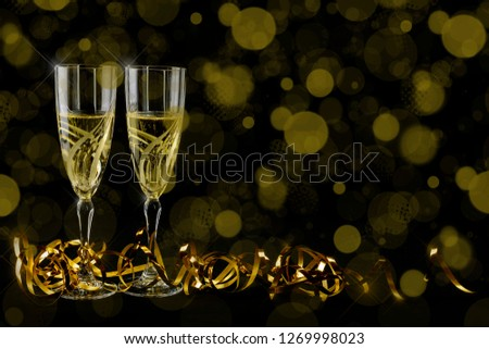 Two crystal bohemian glasses with champagne and golden ribbon. New Year 2019 greetings card. Bokeh and shiny effects on black background. #1269998023