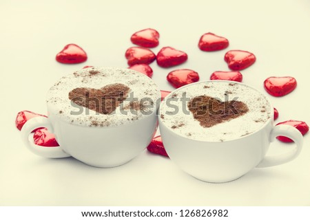 Two cup of coffee with heart symbol and candy around.