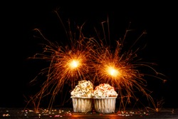 Two cupcakes with sparklers on a black background