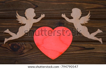 two cupids and a heart made from wood texture background. The holiday of lovers. Valentine's Day. space for text and design #794790547