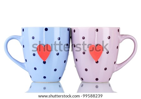 Two cups and tea bags with red heart-shaped label isolated on white