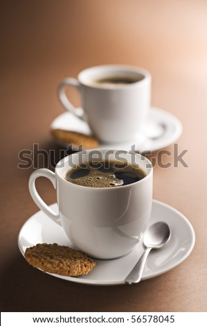 Two cups of black coffee on brown background