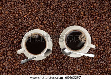 Two cups of black coffee on saucers with coffee spoons standing on roasted coffee beans.