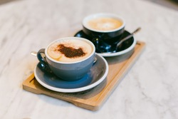 Two cups of cappuccino with cinnamon placed on a little table. Brunch coffee for couple in love. Two mugs of aromatic coffee to relax during coffee break. Delicious flavour of a natural coffee beans.