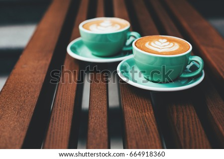 Two cups of cappuccino with latte art on wooden background. Beautiful foam, greenery ceramic cups, stylish toning, place for text. - Shutterstock ID 664918360