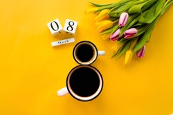 Two cups of coffee, a delicate bouquet of tulips and numbers. Greeting card for Women's Day on March 8. Fashionable yellow background. March 8 and the concept of