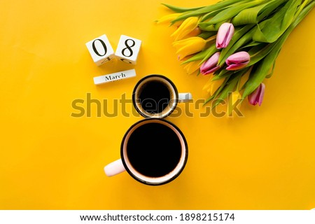 Two cups of coffee, a delicate bouquet of tulips and numbers. Greeting card for Women's Day on March 8. Fashionable yellow background. March 8 and the concept of 'women's day'. Foto stock ©