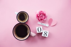 Two cups of coffee, a delicate flower and numbers. Greeting card for Women's Day March 8th. Trendy pink background. March 8 and the concept of