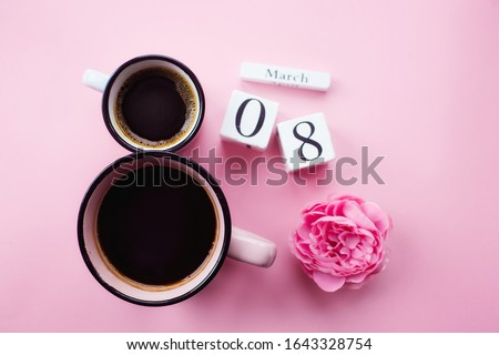 """Two cups of coffee, a delicate flower and numbers. Greeting card for Women's Day March 8th. Trendy pink background. March 8 and the concept of """"Women's Day""""."""