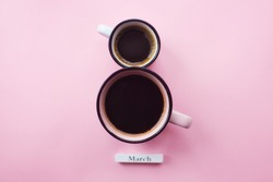 Two cups of coffee and numbers. Greeting card for Women's Day March 8th. Trendy pink background. March 8 and the concept of