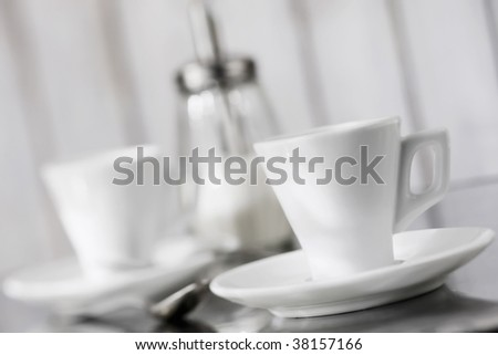 Two cups of coffee on a table with spoon and sugar