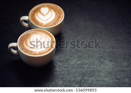 Shutterstock Two cups of coffee on black rustic background with beautiful latte art