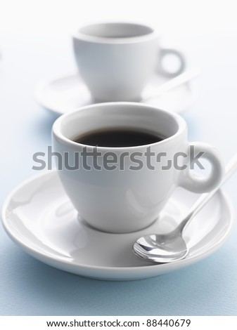 Two cups of coffee on blue background