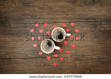 two cups of coffee with red...