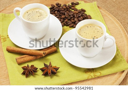 two cups of coffee with star anise and cinnamon