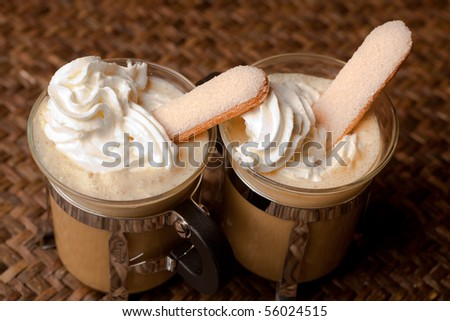 Two cups of coffee with whipped cream and biscuits