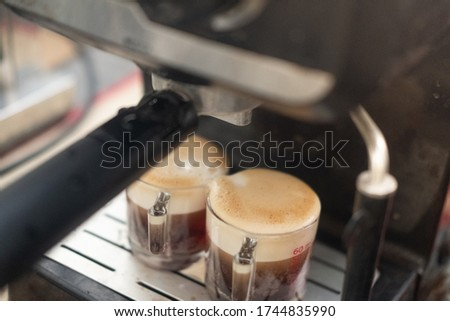 Two cups of espresso poured from a professional espresso machine. Espresso machine brewing a coffee espresso