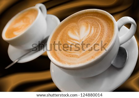 Two cups of gourmet coffee house cappuccino against a silky background