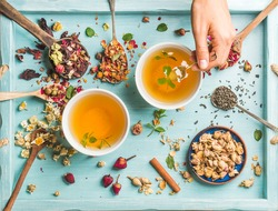 Two cups of healthy herbal tea with mint, cinnamon, dried rose and chamomile flowers in spoons and man's hand holding spoon of honey, blue background, top view