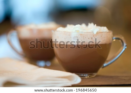 Two cups of hot cocoa or coffee on wood table background