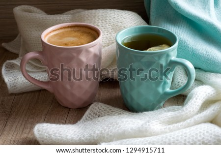Two Cups of hot coffee or cappuccino and hot tea with lemon. Warm scarf a on wooden table. Good morning. Winter mood concept. Warm autumn or winter picture. Time for relax. Coffee vs Tea. Love. Latte.