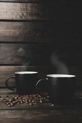 two cups of hot coffee with steam and coffee beans on a wooden and black background. hot drink. steam, warm soft light, dark background, copy space. banner, postcard