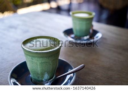 Two cups of hot Matcha latte cuppe on wooden table in a street coffee shop against blurred background. Famous place in Bali Canggu Stok fotoğraf ©