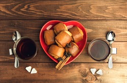 Two cups of tea glass with a metal handle and rolls with cinnamon and sugar cubes in a heart shape on the plate in the form of the heart are on a wooden table
