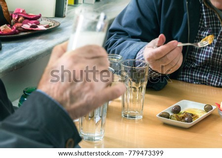 Two customers drinking ouzo with olives (mezedes) inside a traditional Ouzeri Greek tavern.