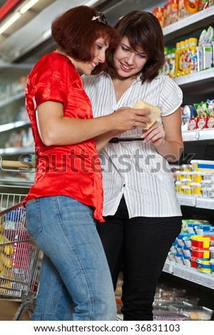 Two customers in supermarket. Focus on the girl in the white.