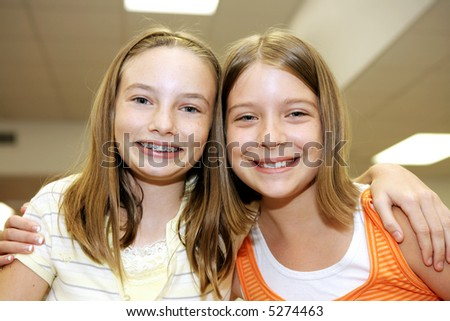 Two cute adolescent girls together in school.