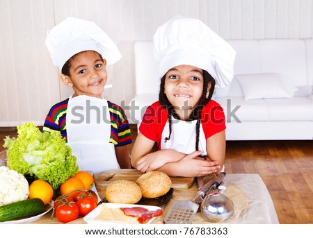 Two cute african american little cooks, ingredients for sandwich in front of them