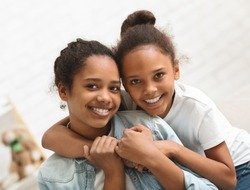 Two cute african american sisters hugging each other at home