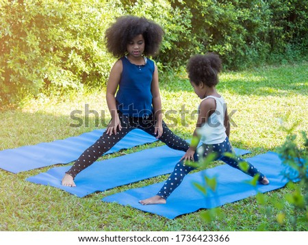 Two cute African with Afro hair siblings sisters doing yoga pose on yoga mat in the garden. Keeping self healthy while staying at home during quarantined. Foto d'archivio ©
