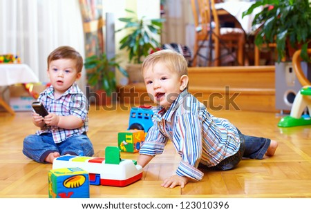 two cute baby boys playing with toys at home