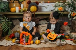 Two cute baby girl dressed in Halloween costume sitting on bed with Halloween decoration at home. Lifestyle indoors portrait of two cute toddler Halloween girls