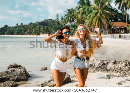 Two cute beautiful girls in Boho style dressed shirts shorts light cape bracelets necklaces, in the hair decorative feathers colored, go embracing the beach against the sea and the rocks #1043662747
