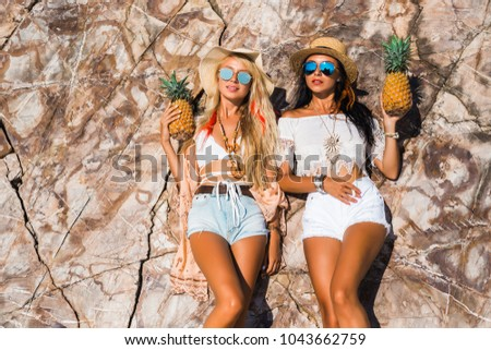Two cute beautiful girls in Boho style dressed shirts shorts light cape bracelets necklaces, in the hair decorative feathers colored, straw hats, with pineapple in their hands on the background cliffs #1043662759